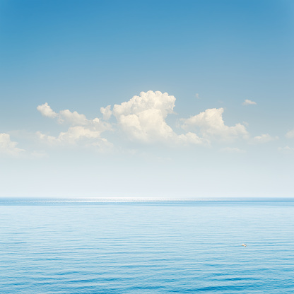 istock blue sea and sky with clouds over it 506246298