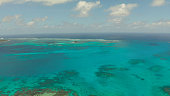Top view of turquoise water of the atoll against the backdrop of the tropical island and sky with clouds. Travel concept.
