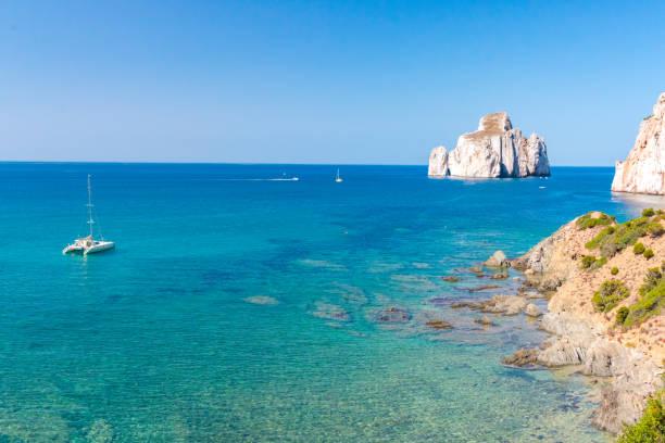 blue sea coast with catamaran and rock island stock photo