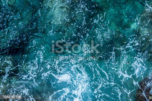 912159408 istock photo Blue sea foaming water background 1044157106