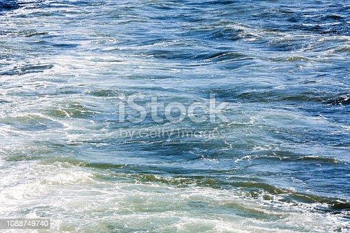 istock Blue sea foaming water background 1088749740