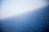 Blue sea from an elevated viewpoint with a small sailboat on a clear and sunny day in summer in a mediterranean island