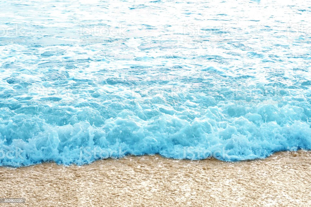 Blue sea water wave coming on the yellow clear clean beach sand stock photo