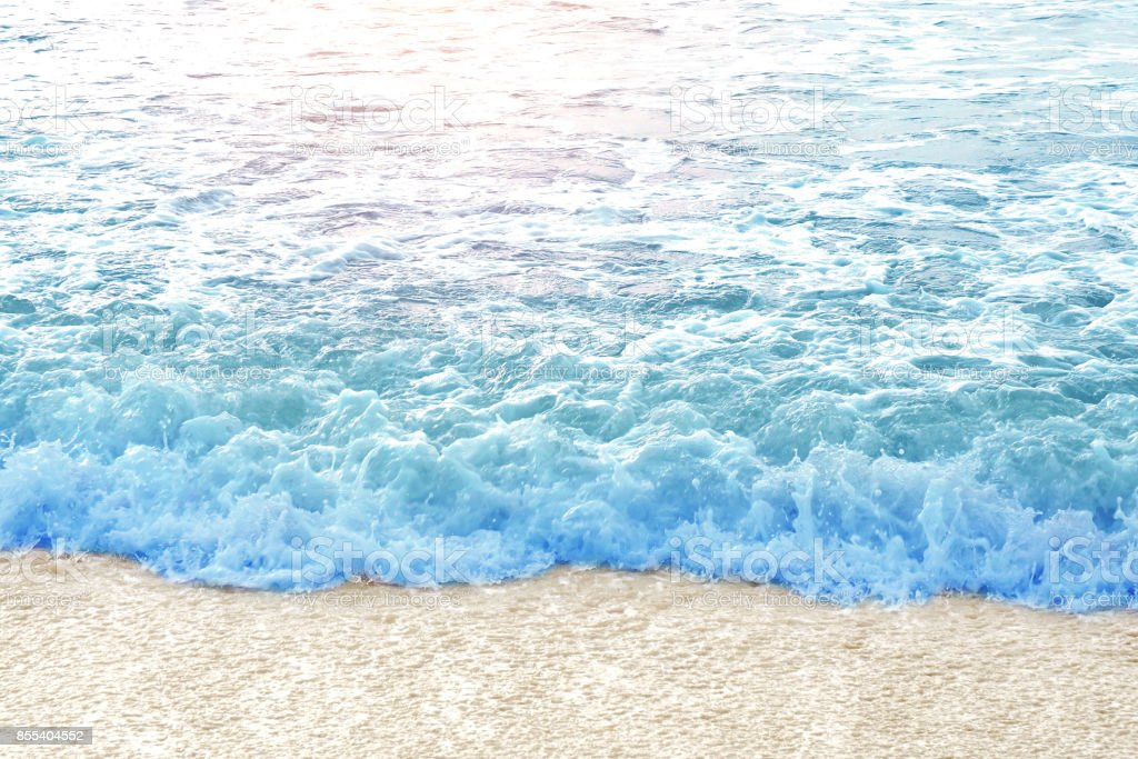 Blue sea water wave coming on the yellow clear clean beach sand with sun light, sunshine stock photo