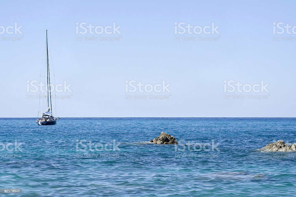 Blue sea with a sailboat royalty-free stock photo