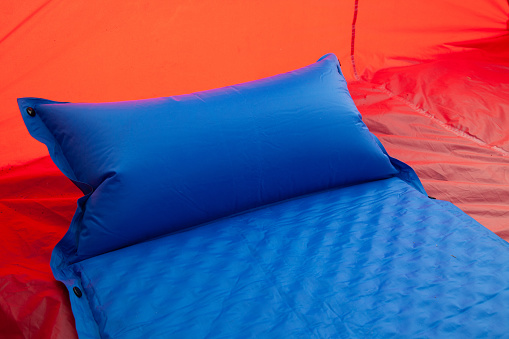 A blue self inflating blow-up mattress pad is placed in a red tent to provide a comfortable sleep to campers or those with a bad back