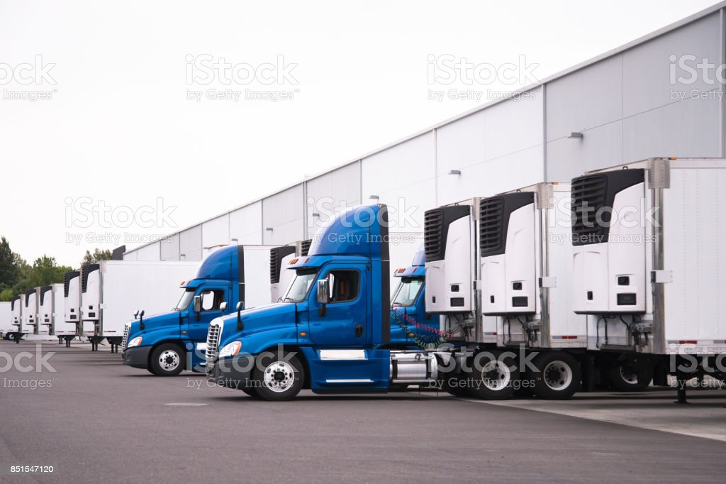 Blue semi trucks and semi trailers stand in row hardly near the warehouse gate under loading and unloading process stock photo