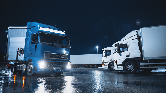Blue Semi-Truck with Cargo Trailer Drives Off From Overnight Parking Space where Other Trucks are Standing. Long Haul Truck Leaves Parking Lot, Transporting Cargo / Goods Across Continent. Rainy Night