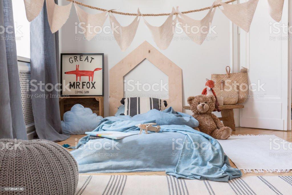 Blaue Blatter Auf Bett Und Grau Hocker Im Kinderzimmer