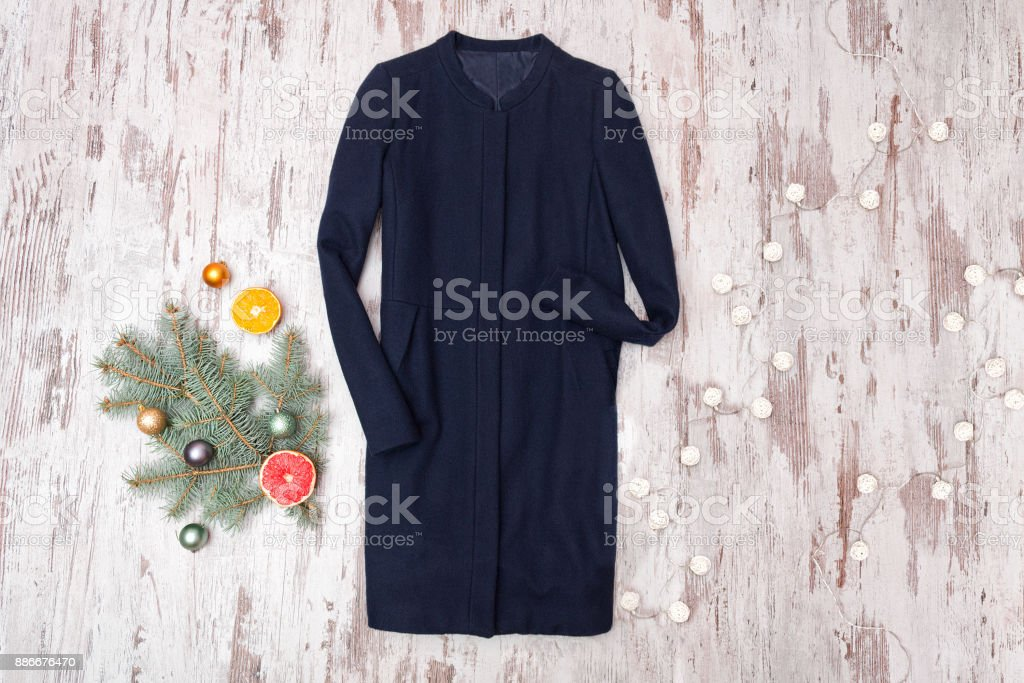 Blue shirt, decorated fir branch and garland on wooden background. Fashionable concept. stock photo