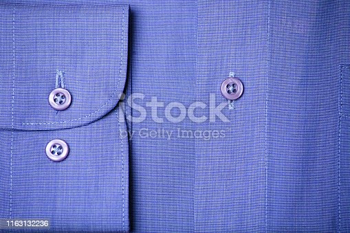 Sleeve and butons detail on a blue elegant shirt.