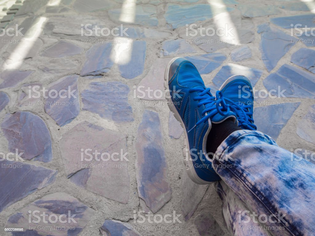 blue shoes foot on  stone background stock photo