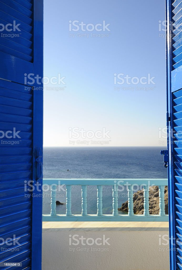 Blue Shutters Open onto Sea and Sky at Dawn stock photo