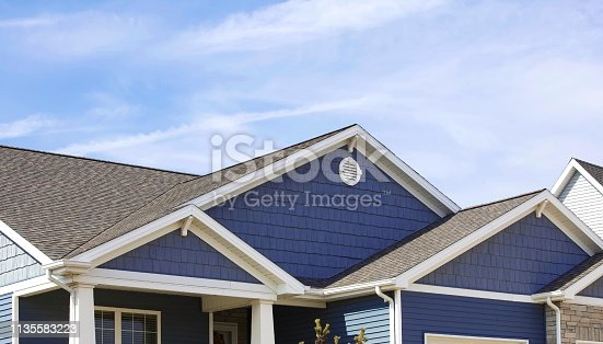 Blue sided contemporary home showing soffit, gutters, roofing, brickwork, and blue sky in the background.