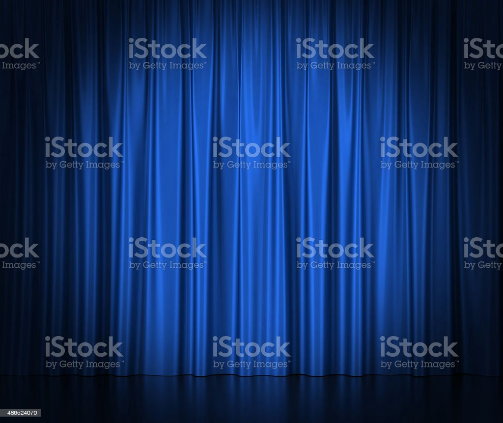 Blue silk curtains for theater and cinema spotlit light in stock photo