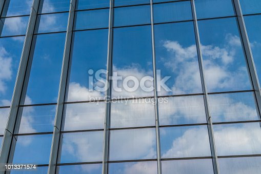 istock Blue sky and clouds reflected at glass wall 1013371574