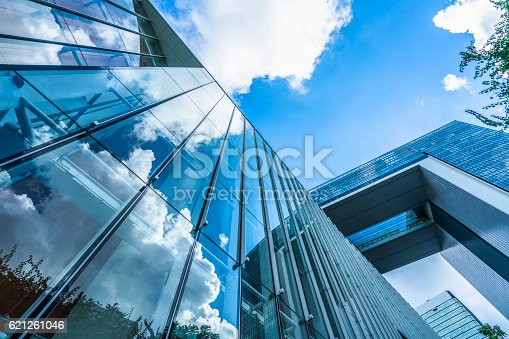istock blue sky and clouds reflected at glass wall 621261046