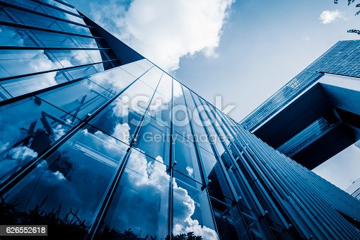 istock blue sky and clouds reflected at glass wall 626552618