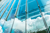 blue sky and clouds reflected at glass wall