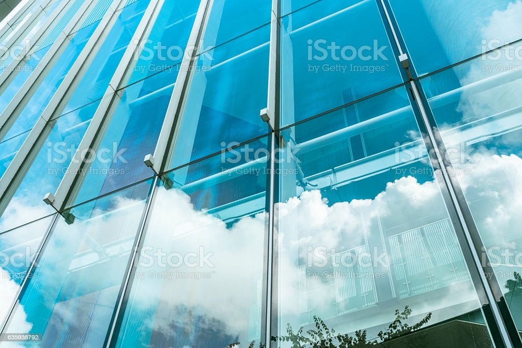 blue sky and clouds reflected at glass wall stock photo