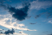 Blue sky and different color clouds in heart shape. Amazing cloudy sky texture background.