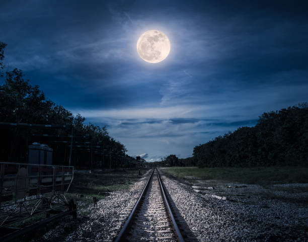 Blue sky and full moon above silhouettes of trees and railway. stock photo