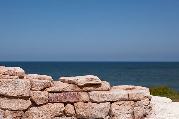 Blue sky and ocean seen behind an orange brick wall stock photo