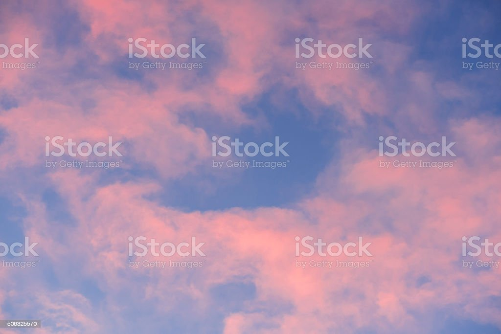 Blue sky and pink and red clouds at sunrise stock photo
