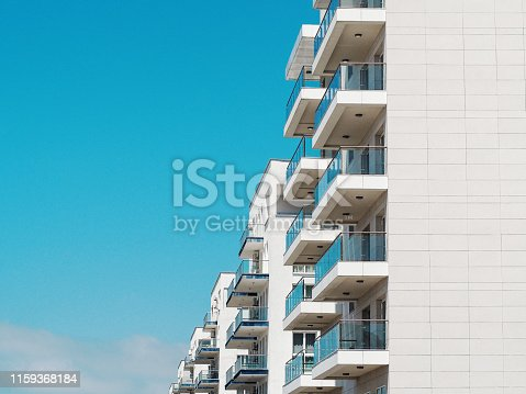 Symmetry of blue sky and residential house. Urban background with apartment building