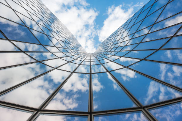 blue sky and white clouds reflecting in a  glass buildin - diminishing perspective stock pictures, royalty-free photos & images