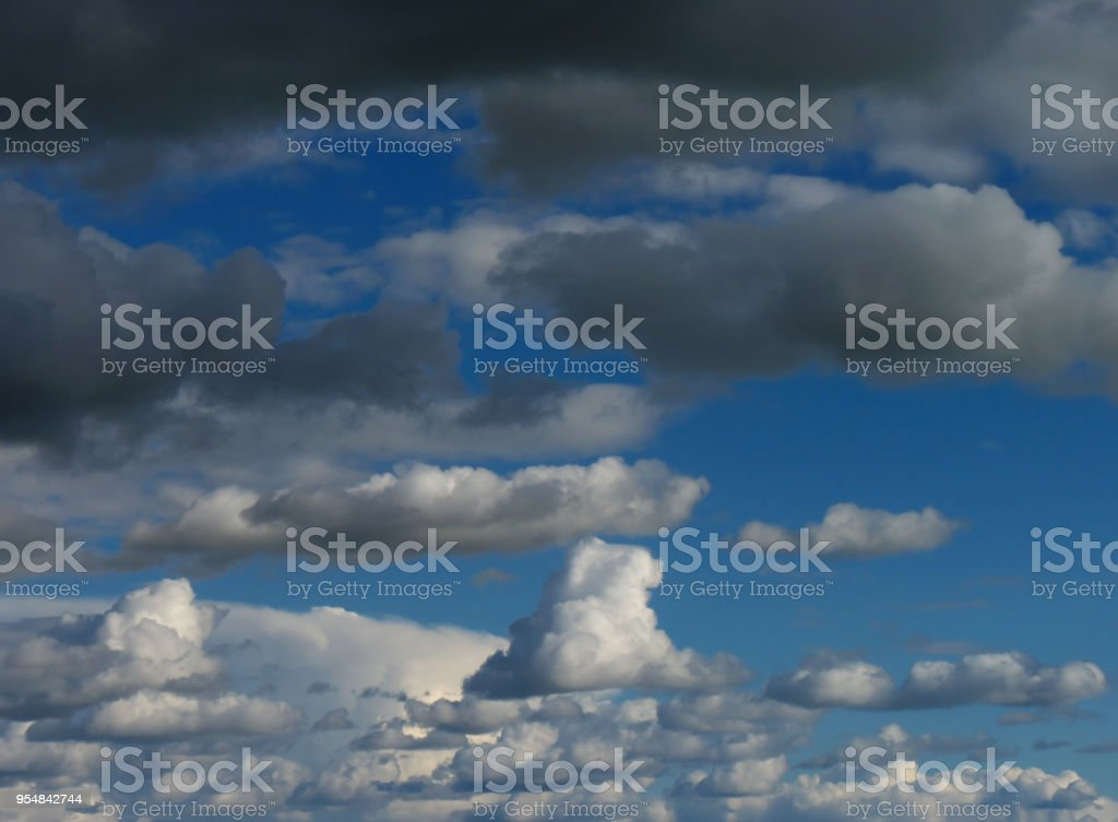 Blue sky background with gray clouds and fluffy white clouds. Cumulus stock photo