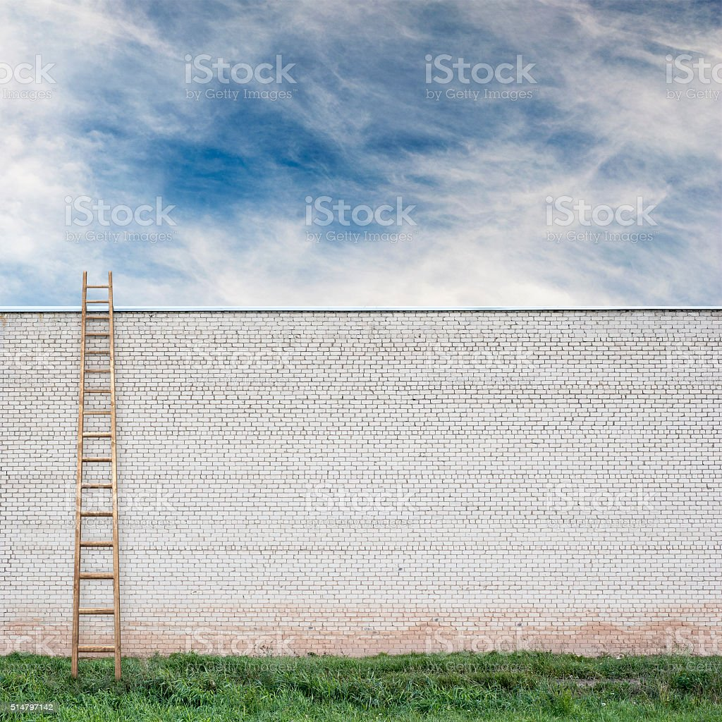 Blue sky behind the huge wall with a wooden ladder stock photo