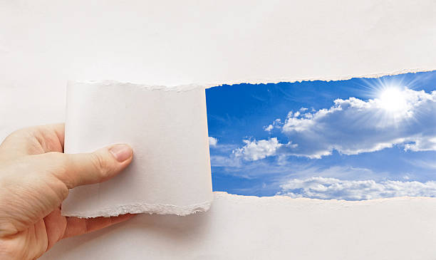 blue sky behind torn paper stock photo
