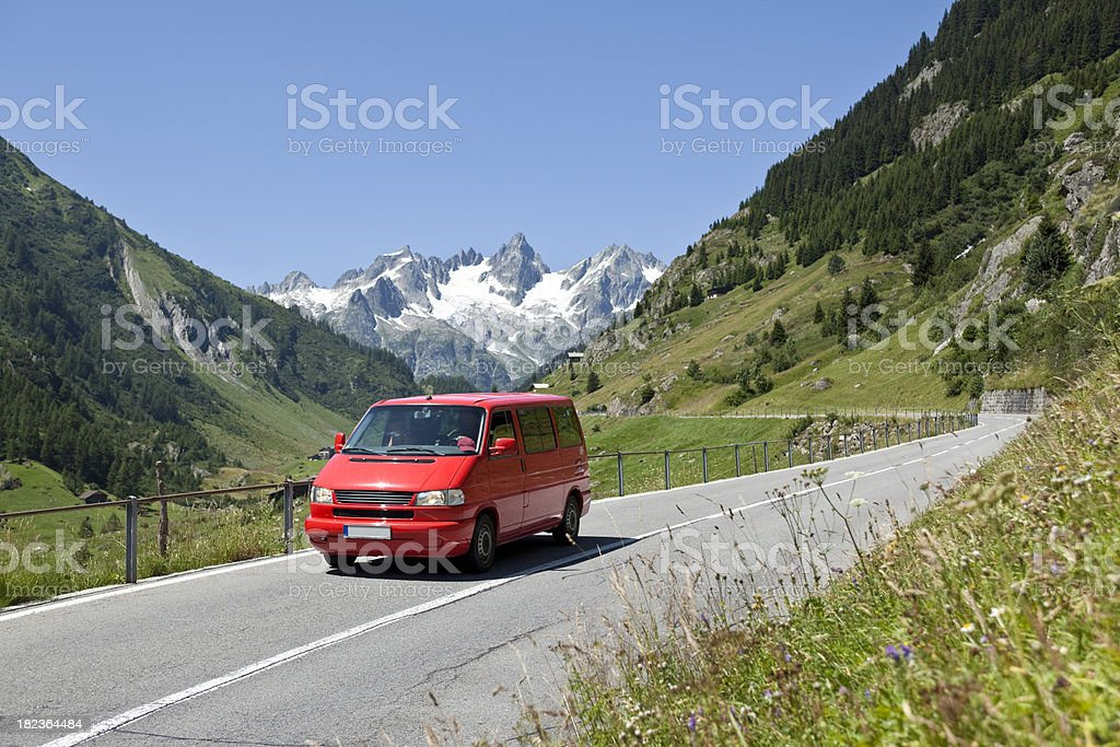 Blue sky over red delivery van crossing the alpes royalty-free stock photo