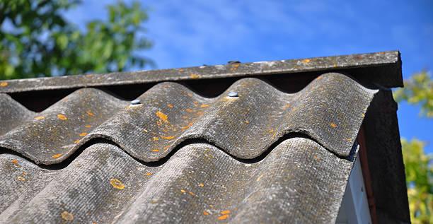 blauer himmel über alte fliesen gefährliche asbest dach  - dachschräge einrichten stock-fotos und bilder