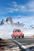 El Chalten, Argentina - February 13, 2010: Young couple driving in a pink Volkswagen beetle Type 1 through Patagonia Argentina. In the background Mt. Fitz Roy. 21,529,464 beetle were produced from 1938 until 2003.