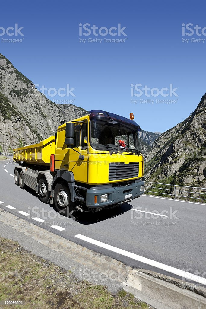 Blue sky over yellow truck crossing suisse alpes royalty-free stock photo