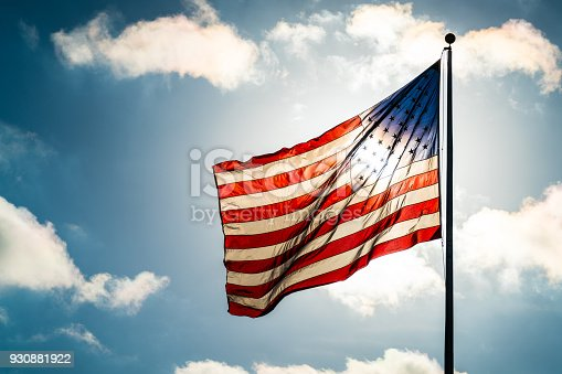 close up on mainly flag in the frame with a few clouds - Looking directly into Sunlight American Flag glowing in the direct sun - Blue Sky, Puffy Clouds, and American Flag waving into the Sunshine