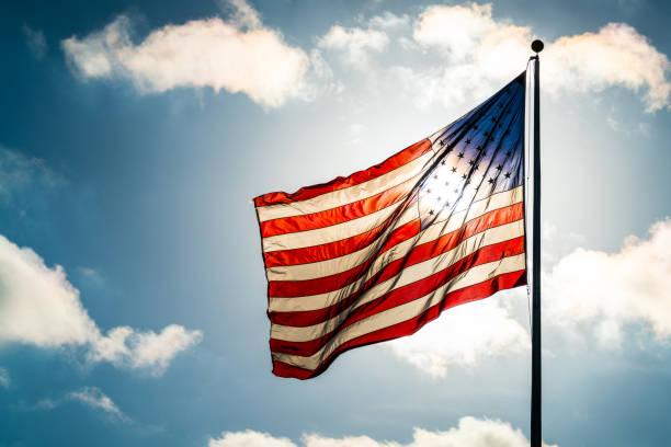 blauer himmel, geschwollenen wolken und amerikanische flagge winken in den sonnenschein hautnah - pfosten stock-fotos und bilder