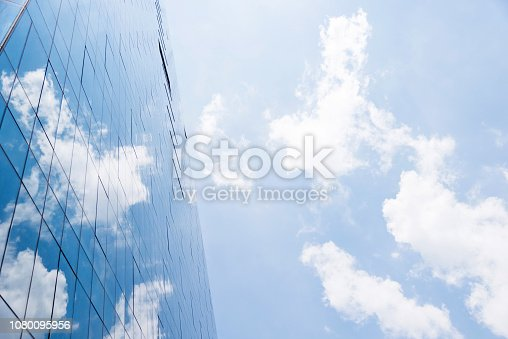 Blue sky reflected on wall of modern office building.