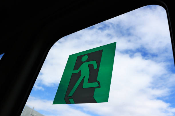 Blue sky spread behind the pictograph of emergency exit stock photo