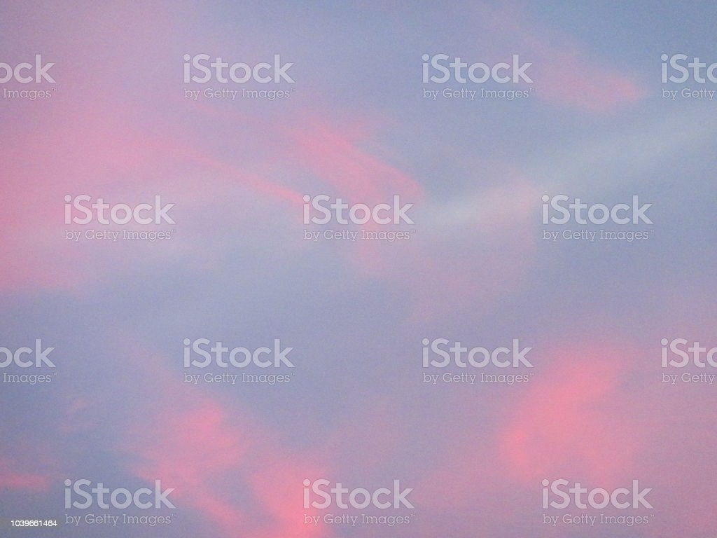 Blue sky sunset with swirly pink clouds stock photo