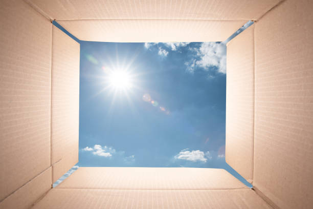 Blue sky viewed from inside of a cardboard box. stock photo