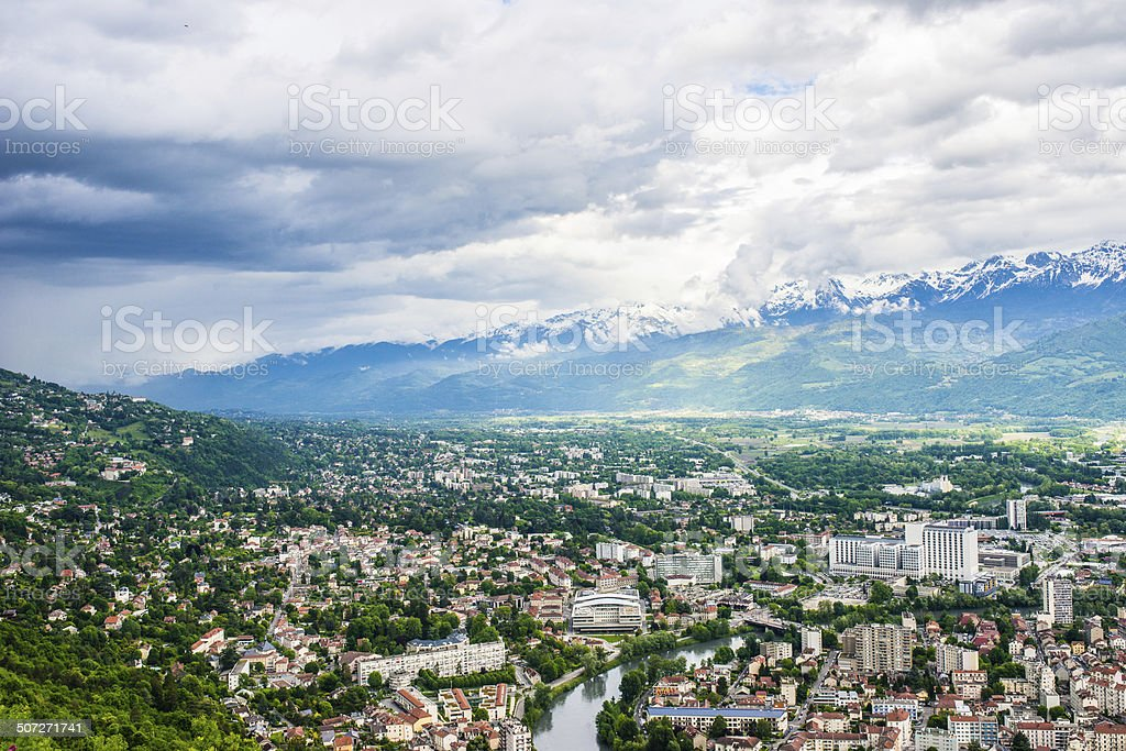 Blue sky, white clouds, icy mountain and green forest stock photo