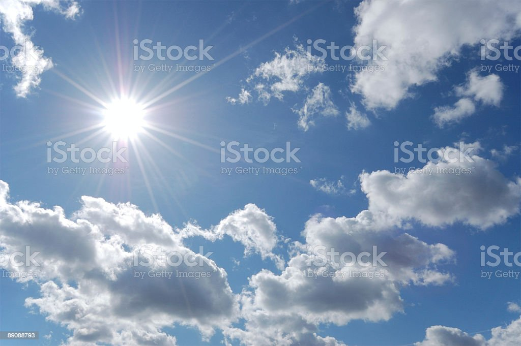Blue sky with a few white clouds and the sun is shining royalty-free stock photo