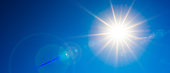 Hot summer or heat wave background, wonderful blue sky with glowing sun and clouds