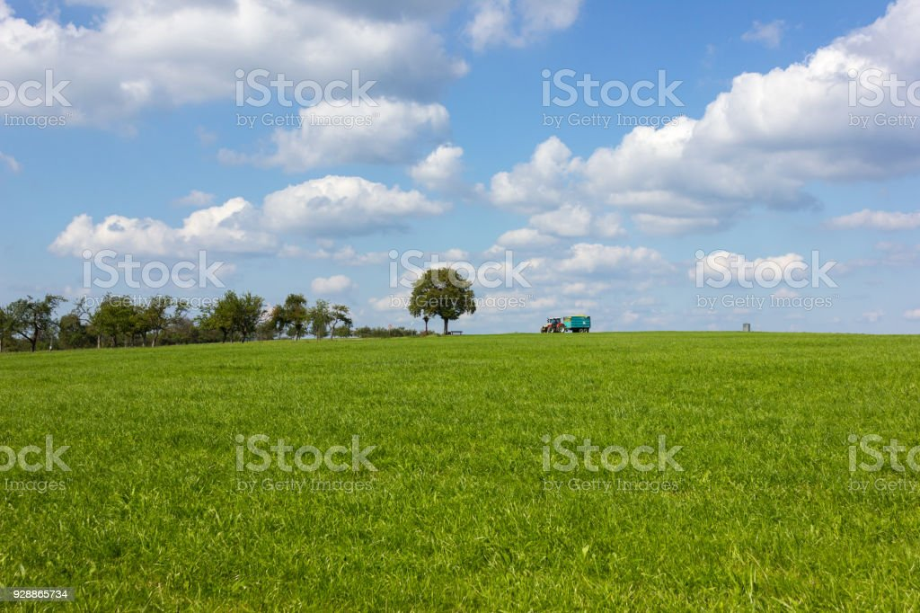 blue sky with clouds and green field and tractor on horizon stock photo
