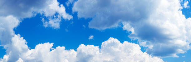 Blue sky with cumulus fluffy white clouds. Panoramic photo stock photo