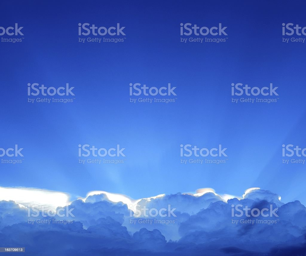 Blue sky with dramatic sunbeams and clouds royalty-free stock photo
