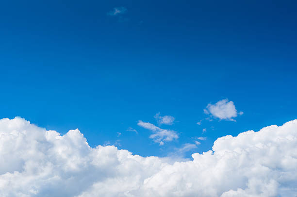 Blue sky with dramatic white clouds below stock photo